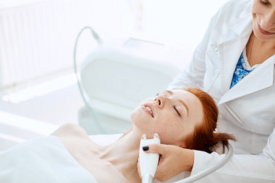 professional in white uniform performing hydro facial treatment for a red haired caucasian woman lying on the coach