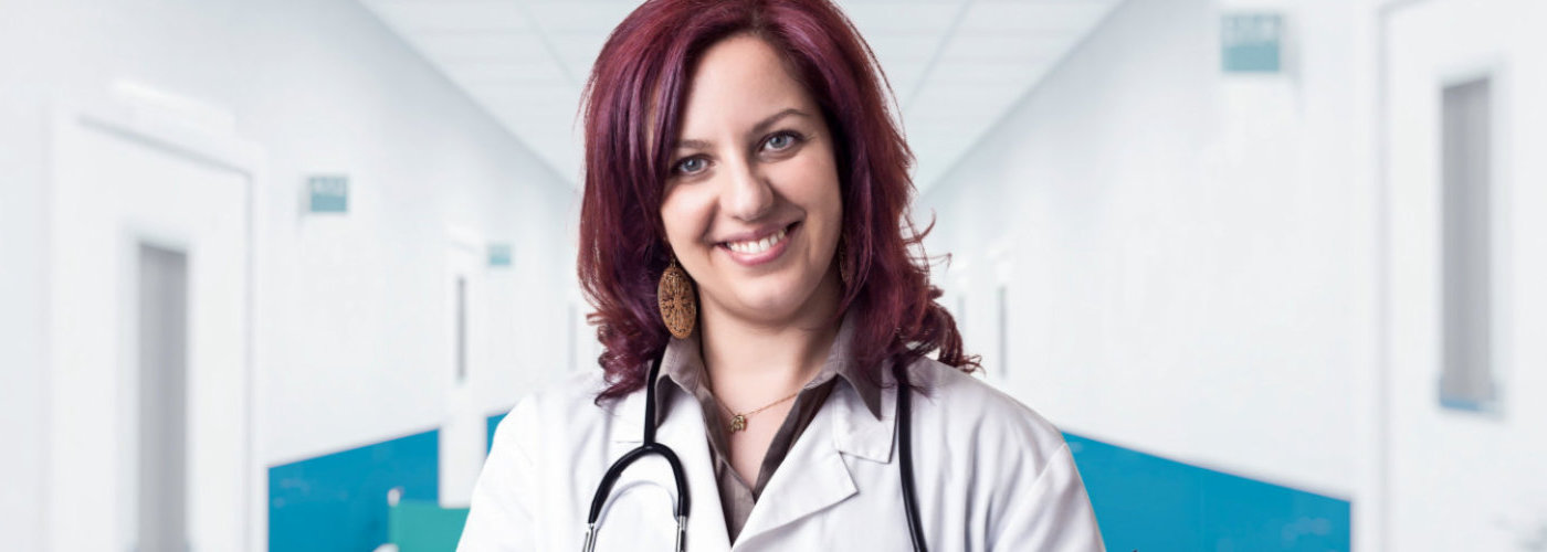 female doctor wearing stethoscopes smiling